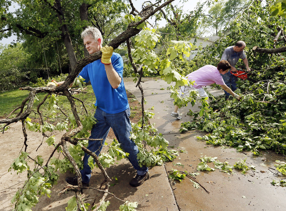 Photo - Brad Avey clears fallen trees from his property, 2700 Old Farm Rd., after a tornado moved through Edmond, Okla., Sunday, May 19, 2013. Photo by Nate Billings, The Oklahoman