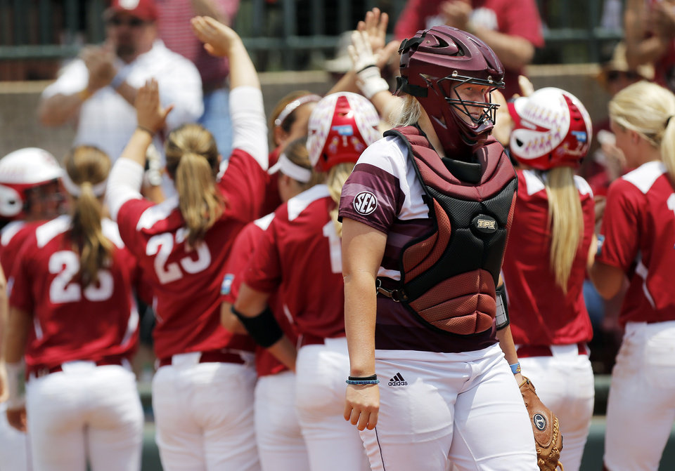 Photo - The OU Sooners celebrate behind Texas A&M catcher Nicole Morgan (25) after three runs scored in the 2nd inning during the final game of the Norman Regional in 2014 NCAA softball championship between Oklahoma and Texas A&M in Norman, Okla., Sunday, May 18, 2014. OU won 11-6. Photo by Nate Billings, The Oklahoman