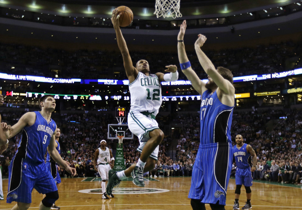 Boston Celtics guard Leandro Barbosa (12) drives to the basket against Orlando Magic forward Josh McRoberts, right, during the first quarter of an NBA basketball game in Boston, Friday, Feb. 1, 2013. At left is Magic center Nikola Vucevic. (AP Photo/Charles Krupa)