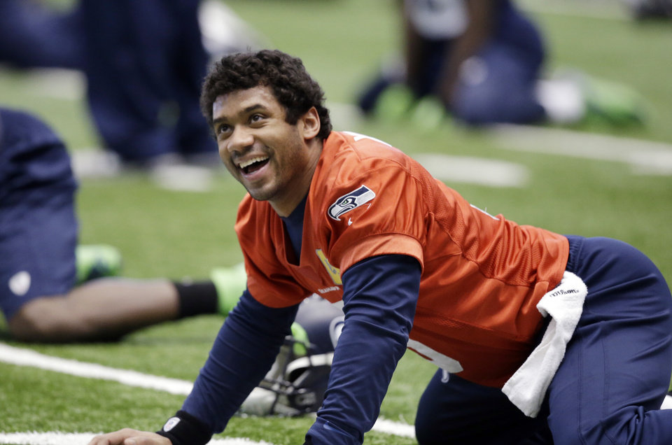 Photo - Seattle Seahawks quarterback Russell Wilson smiles as he stretches at an NFL football practice Tuesday, Jan. 7, 2014, in Kirkland, Wash. The Seahawks play the New Orleans Saints Saturday in an NFC divisional playoff game. (AP Photo/Elaine Thompson)