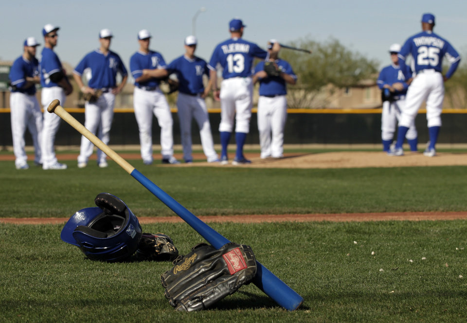 Photo - Kansas City Royals batting equipment sits on the field as pitchers prepare for drills during spring training baseball practice, Saturday, Feb. 15, 2014, in Surprise, Ariz. (AP Photo/Tony Gutierrez)