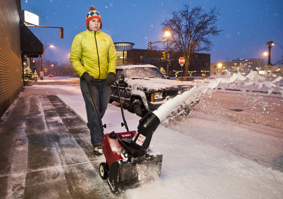 Steven Dedomenic clears a sidewalk along Seventh Street on Friday, Dec. 6, 2013, in downtown Columbus, Ind.  Several inches of snow fell on central and southern Indiana, making driving treacherous and leading to at least two fatal crashes. (AP Photo/The Republic, Andrew Laker)
