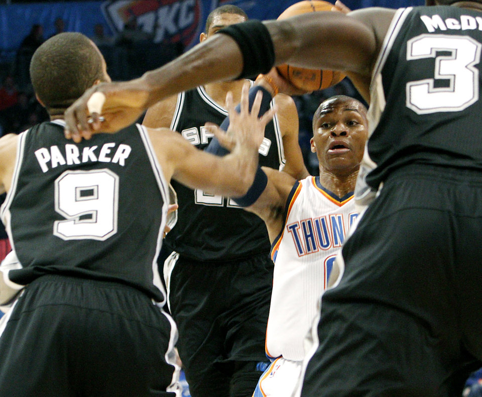 Photo - Oklahoma City's Russell Westbrook is surrounded by San Antonio's defense during their NBA basketball game in downtown Oklahoma City  on Sunday, Nov. 14, 2010.Photo by John Clanton, The Oklahoman