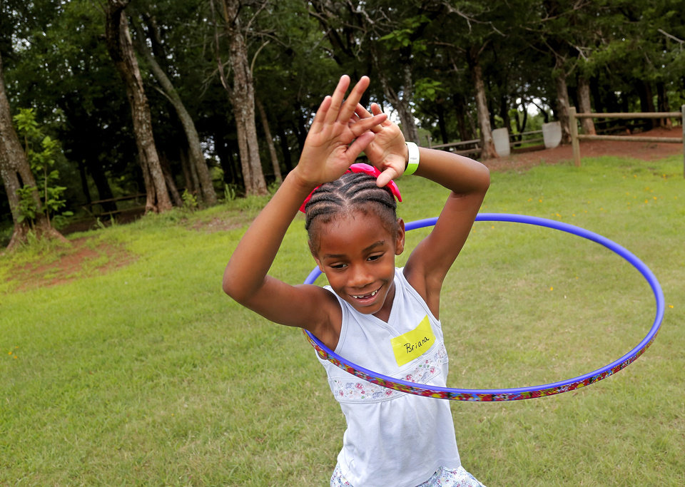 Photo -  A girl spins a Hula-Hoop at an Outdoor Adventure Day hosted by the nonprofit Redeeming the Family, for children who have a parent serving a prison term.  Photo by Jim Beckel, The Oklahoman   Jim Beckel -  THE OKLAHOMAN
