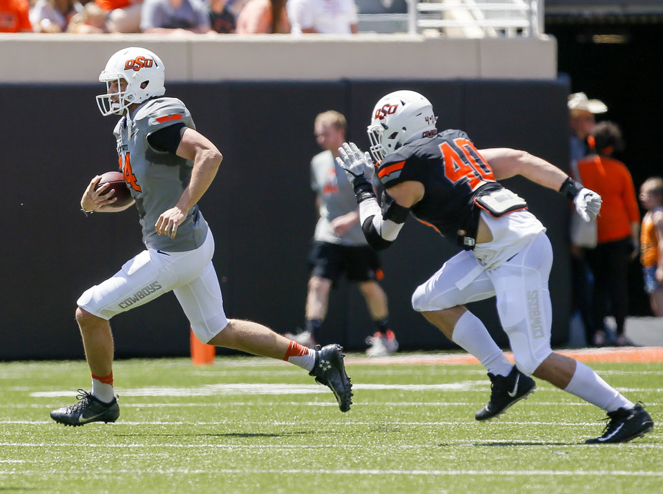 Photo - Taylor Cornelius (14) carries the ball away from Brock Martine (40) during the spring football game for the Oklahoma State Cowboys (OSU) at Boone Pickens Stadium in Stillwater, Okla., Saturday, April 28, 2018. Photo by Nate Billings, The Oklahoman