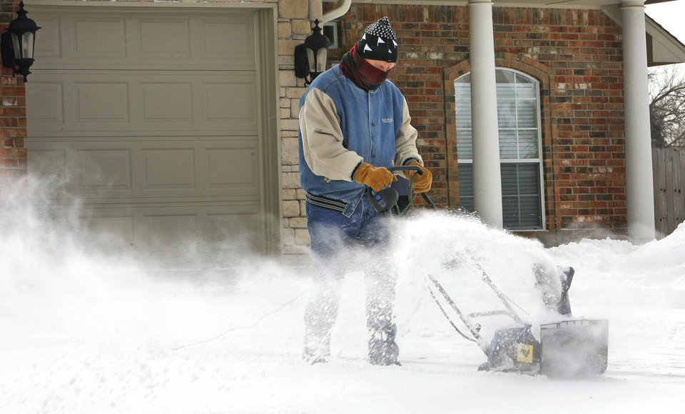 Photo - John McCurley uses a borrowed snow blower to clean his drive as the second round of snow in a week moved into the area on Wednesday, February 9, 2011, in Newcastle, Okla.   Photo by Steve Sisney, The Oklahoman