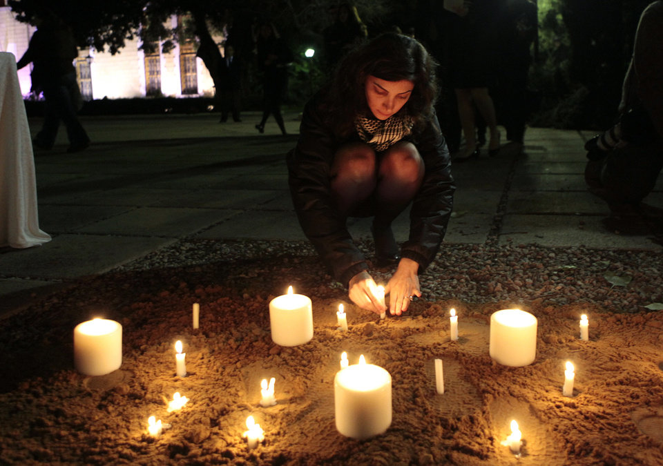 Photo - Nada Bakri,  wife of Anthony Shadid who was the New York Times Beirut Bureau Chief, lights candles after a memorial ceremony for her husband at the American University of Beirut, Lebanon, on Tuesday Feb. 21, 2012. Shadid died Thursday, Feb. 16, 2012, apparently of an asthma attack, while on assignment for the New York Times in Syria, the paper said. He was 43. (AP Photo/Hussein Malla) ORG XMIT: BEI105