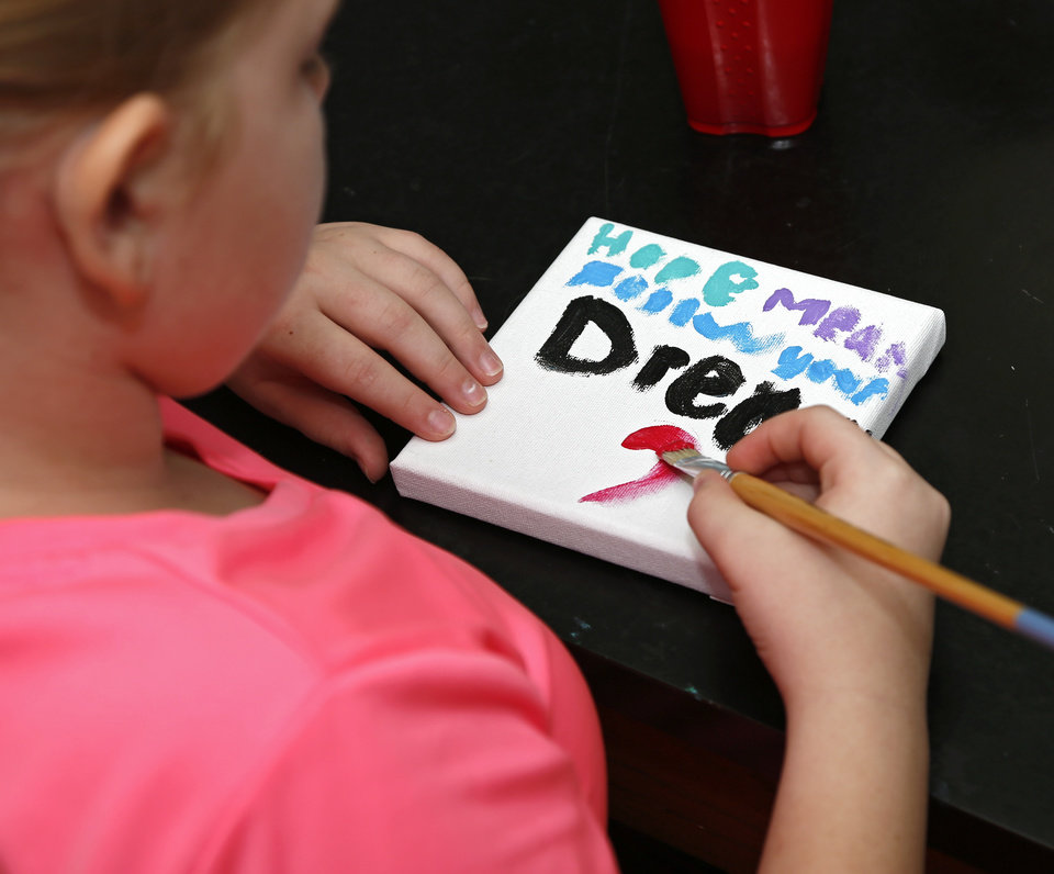 "Photo -  Madison, 10, paints a heart below where she painted, ""Hope means follow your dream,"" during an arts and crafts time at Camp Hope Oklahoma City. [Photo by Kurt Steiss, The Oklahoman]"