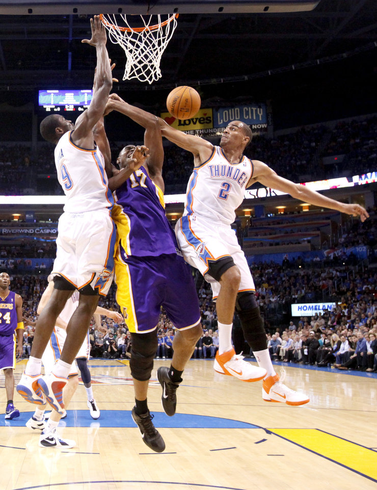 Photo - Oklahoma City's Serge Ibaka (9) and Thabo Sefolosha (2) Lakers' Andrew Bynum (17) during the NBA basketball game between the Oklahoma City Thunder and the Los Angeles Lakers, Sunday, Feb. 27, 2011, at the Oklahoma City Arena.Photo by Sarah Phipps, The Oklahoman