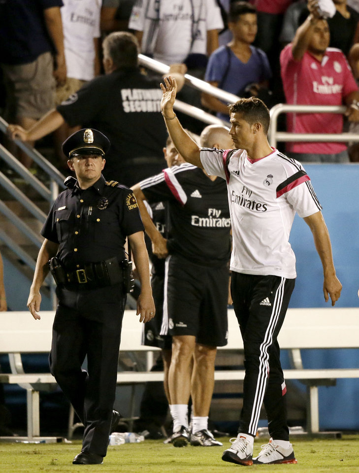 Photo - Real Madrid's Cristiano Ronaldo waves to fans as a police officer escorts him and the team off the field after their 1-0 loss to Roma in a Guinness International Champions Cup soccer tournament match, Tuesday, July 29, 2014, in Dallas. (AP Photo/Tony Gutierrez)