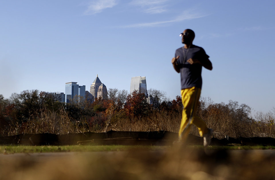Photo -   In this Nov. 20, 2012 photo, a jogger runs along the Atlanta BeltLine as midtown high-rises stand in the background in Atlanta. Since an Atlanta nonprofit opened a 2.25-mile-long paved trail east of downtown last month, it has attracted a steady stream of joggers, dog-walkers and cyclists to take in spectacular views of the skyline as well as a slice of established neighborhoods that were once only seen by riding a freight train. The Eastside Trail is the latest and most visible phase of the Atlanta BeltLine, an ambitious $2.8 billion plan to transform a 22-mile railroad corridor that encircles Atlanta into a network of parks, trails, public art, affordable homes and ultimately streetcars. (AP Photo/David Goldman)