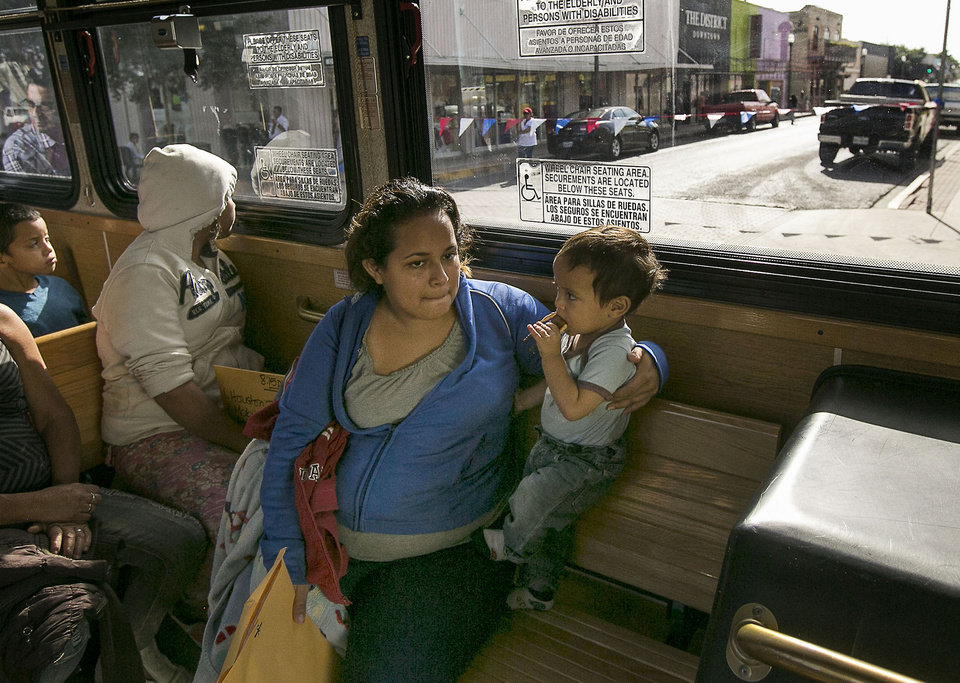 Photo - In this photo taken July 4, 2014, Marta Beltran, 19, of El Salvador, holds her 18-month-old son, Lenny, as they ride a city shuttle bus from the McAllen city bus station to the Sacred Heart Catholic Church Shelter in McAllen, Texas. About 90 Hondurans a day cross illegally from Mexico into the U.S. at the Rio Grande near McAllen, according to the Honduran Consulate, and the families are then brought to Central Station in McAllen and each is released on their own recognizance. Though most travelers have enough money to purchase their own bus tickets to meet family in cities across the U.S., many have nowhere to stay before the buses leave, and most are in need of rest, medical attention and sustenance. It falls to the local government and charities to welcome the uninvited visitors to America. Tens of thousands have also fled to the U.S. from El Salvador and Guatemala to escape violence.  (AP Photo/Austin American-Statesman, Rodolfo Gonzalez)
