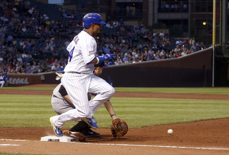 Photo - Chicago Cubs' Emilio Bonifacio beats the throw from Colorado Rockies second baseman DJ LeMahieu to first baseman Justin Morneau, during the second inning of a baseball game Tuesday, July 29, 2014, in Chicago. (AP Photo/Charles Rex Arbogast)