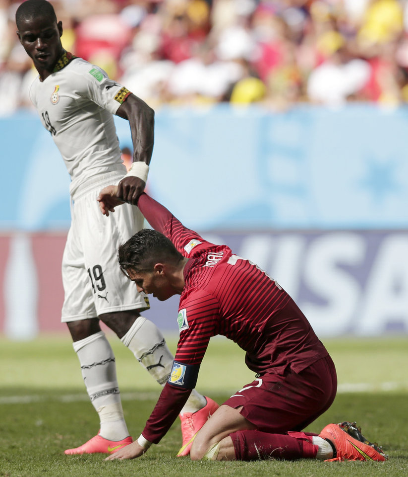 Photo - Ghana's Jonathan Mensah helps Portugal's Cristiano Ronaldo to get up after Ronaldo missed a chance to score during the group G World Cup soccer match between Portugal and Ghana at the Estadio Nacional in Brasilia, Brazil, Thursday, June 26, 2014. Ronaldo's first goal of the World Cup earned Portugal a 2-1 win over Ghana but couldn't prevent his team being eliminated from the tournament along with the Africans on Thursday. (AP Photo/Marcio Jose Sanchez)