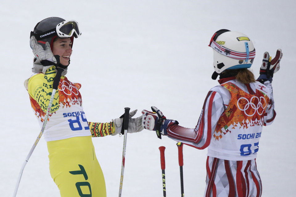 Photo - Togo's Alessia Afi Dipol and Albania's Suela Mehilli celebrate after completing the first run in the women's giant slalom at the Sochi 2014 Winter Olympics, Tuesday, Feb. 18, 2014, in Krasnaya Polyana, Russia. (AP Photo/Gero Breloer)