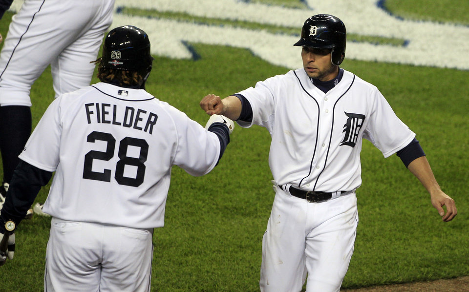 Photo -   Detroit Tigers' Omar Infante, right is congratulated by teammate Prince Fielder after scoring on a fielding error by Oakland Athletics starting pitcher Jarrod Parker during the third inning of Game 1 of the American League division baseball series, Saturday, Oct. 6, 2012, in Detroit. (AP Photo/Carlos Osorio)