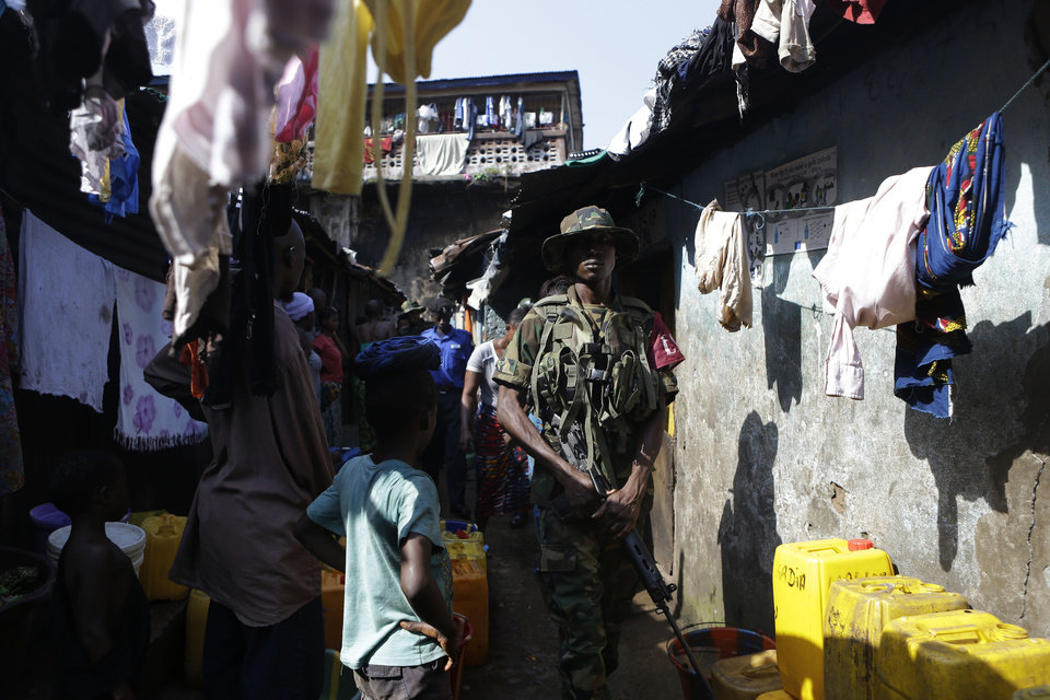Photo -   Security forces walk through the Mabella slum after breaking up a domestic dispute and arresting several residents, in Freetown, Sierra Leone Friday, Nov. 16, 2012. Ten years after the end of a devastating civil war, Sierra Leone will go to the polls on Saturday to choose between candidates including incumbent President Ernest Bai Koroma and opposition leader Julius Maada Bio. With maintaining a peaceful atmosphere around the vote a top priority, the police force, reinforced by other security forces, is taking a proactive approach. (AP Photo/Rebecca Blackwell)