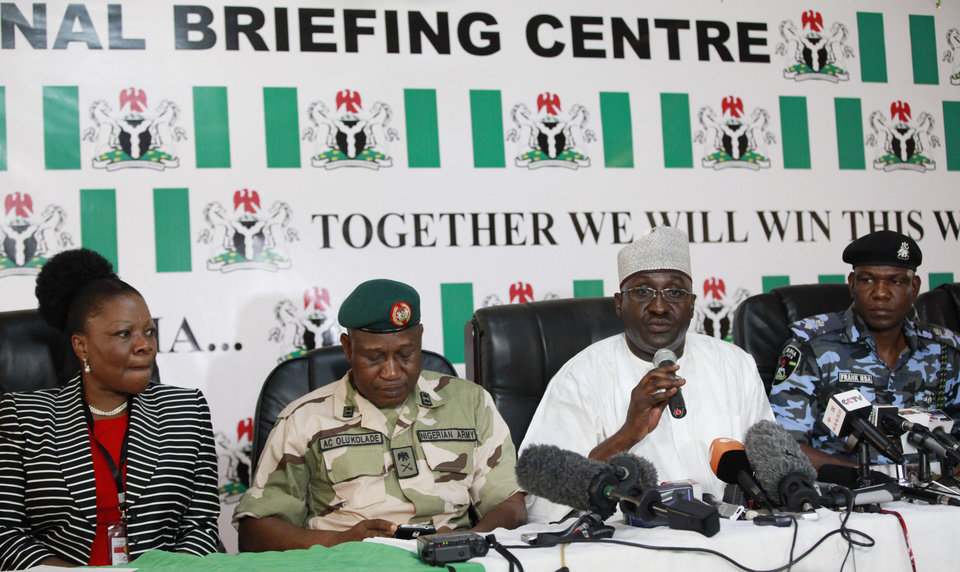 Photo - Marilyn Ogar, Secret police spokeswoman, left, Brig. Gen. Chris Olukolade, Nigeria's top military spokesman, 2nd left,  Mike Omeri, Director General, National Orientation Agency, 2nd right, and Frank Mba, National police spokesman, attend a press conference on the abducted school girls in Abuja, Nigeria, Monday, May 12, 2014. A Nigerian Islamic extremist leader says nearly 300 abducted schoolgirls will not be seen again until the government frees his detained fighters. A new video from Nigeria's homegrown Boko Haram terrorist network received Monday purports to show some of the girls and young women chanting Quranic verses in Arabic. The barefoot girls look frightened and sad and sit huddled together wearing gray Muslim veils. Some Christians among them say they have converted to Islam. (AP Photo/Sunday Alamba)