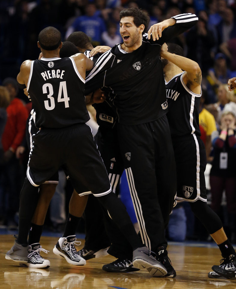 Photo - Nets players pile on Joe Johnson after his game winning shot during an NBA basketball game where the Oklahoma City Thunder were defeated 95-93 by the Brooklyn Nets at the Chesapeake Energy Arena in Oklahoma City, on Thursday, Jan. 2, 2014. Photo by Steve Sisney The Oklahoman