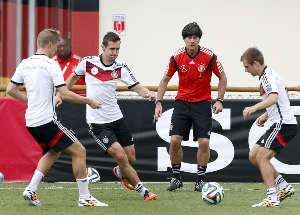 Photo - German national soccer players Tonis Kroos, from left, Miroslav Klose, head coach Joachim Loew and captain Philipp Lahm challenge for the ball during a training session in Santo Andre near Porto Seguro, Brazil, Monday, June 23, 2014. Germany play in group G of the 2014 soccer World Cup. (AP Photo/Matthias Schrader)