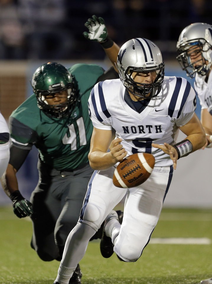 Photo - Edmond North's Luke Hoskins fumbles the ball as Edmond Sante Fe's Alvin Bazley defends during high school football game between Edmond Santa Fe and Edmond North at Wantland Stadium in Edmond, Okla.,  Friday, Sept. 14, 2012. Photo by Sarah Phipps, The Oklahoman