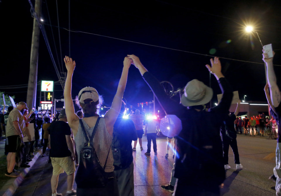 Photo - Protestors raise their arms in the air near NW 23rd and Penn in Oklahoma City, Saturday, May 30, 2020. The protest was in response to the death of George Floyd. [Sarah Phipps/The Oklahoman]