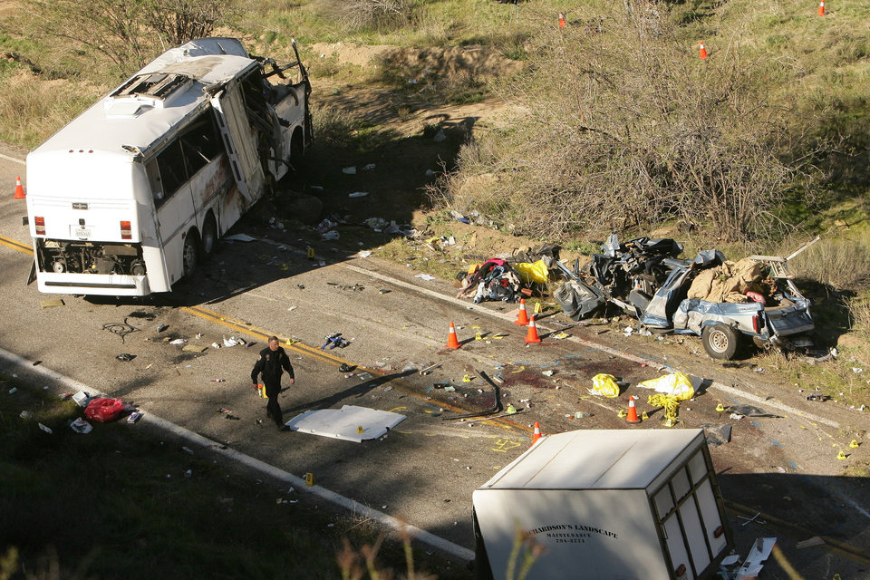 Photo - Investigators continue to work the scene of a bus crash that happened overnight on Highway 38 that killed at least 8 people on Monday, Feb. 4, 2013. California Highway Patrol spokesman Mario Lopez said Monday morning that the number of eight confirmed deaths was expected to rise because the coroner was just starting to remove bodies from the mangled vehicles and also take away the remains of those who were ejected. (AP Photo/The Press-Enterprise, Stan Lim)  NO SALES; MAGS OUT; MANDATORY CREDIT