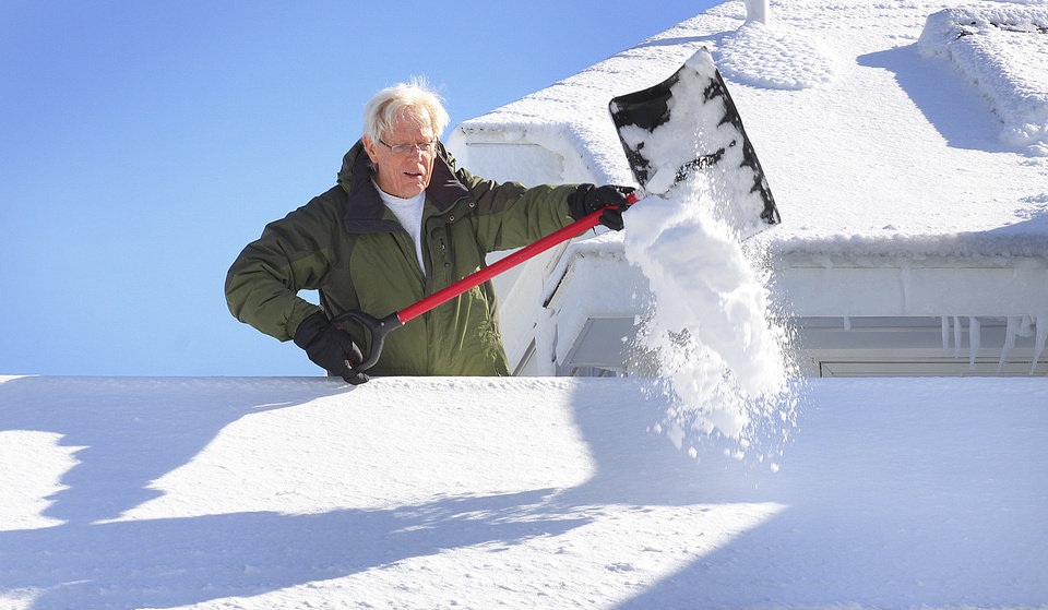 Jim Barrow shovels snow from the roof of his home on Allerton Hill in Hull, Mass., Sunday, Feb. 10, 2013, after more than two feet of snow blanketed the region from a storm that ended Saturday. (AP Photo/The Patriot Ledger, Gary Higgins)  BOSTON OUT