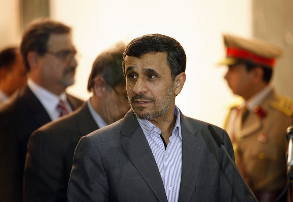 Photo - Iran's President Mahmoud Ahmadinejad, center, arrives to participate in a press conference with Iraqi Vice President Khudier al-Khuzaie, not shown, in Baghdad, Iraq, Thursday, July 18, 2013. Iran's outgoing President Mahmoud Ahmadinejad has landed in Iraq on his second visit as head of government, highlighting the growing ties between the two Shiite-led neighbors. (AP Photo/ Hadi Mizban, Pool)