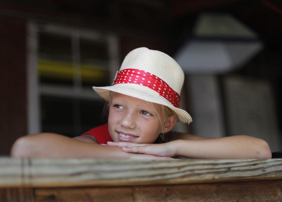 Photo -  CHILD / CHILDREN / KIDS: Brooke Teter, 10, of Wichita Kansas, watches a performance during the Woody Guthrie Folk Festival in Okemah, Okla., Thursday, July 12, 2012.  Photo by Garett Fisbeck, The Oklahoman