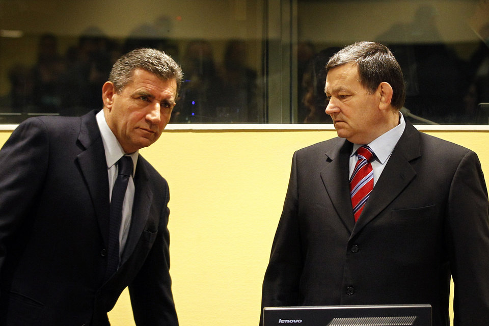Photo -   Former Croatian Army Generals Ante Gotovina, left, and Mladen Markac, right, enter the courtroom of the Yugoslav war crimes tribunal (ICTY) for their appeal judgement in The Hague, Netherlands, Friday, Nov. 16, 2012. The ICTY is delivering its decision in the appeal of two Croatian generals convicted for their roles in a 1995 military offensive to drive Serb rebels out of land they had occupied for years along part of Croatia's border with Bosnia. Gotovina and Markac, were sentenced to 24 and 18 years respectively in 2011 for war crimes and crimes against humanity. (AP Photo/Bas Czerwinski, Pool)