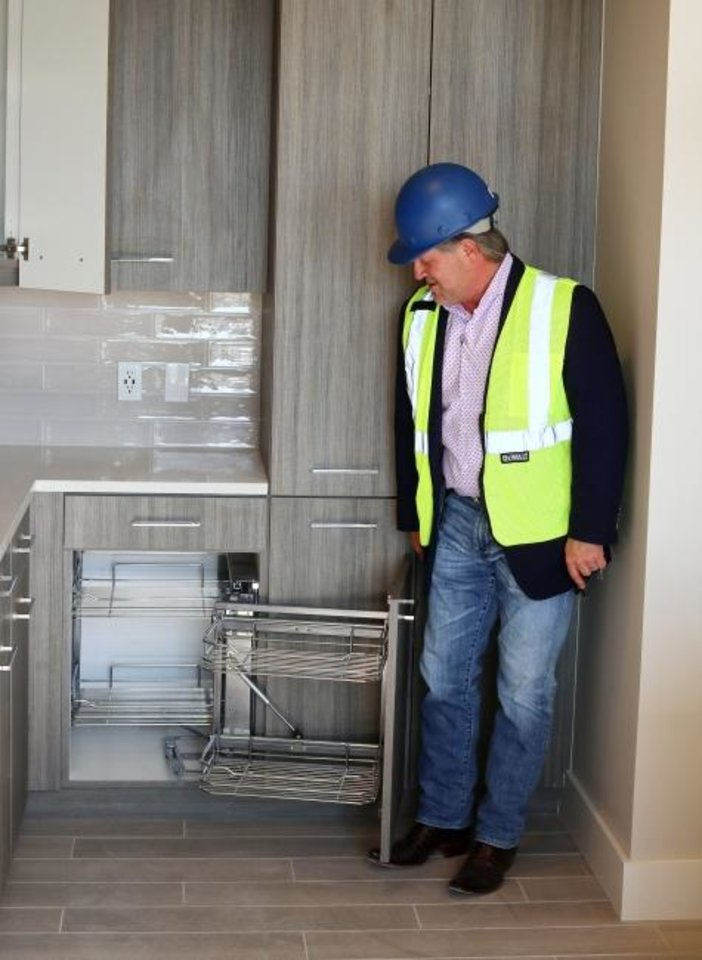Photo -  First National developer Gary Brooks inspects kitchen cabinets in a completed apartment. [DOUG HOKE/THE OKLAHOMAN]