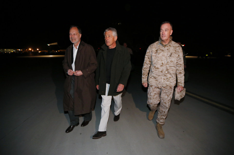 Photo - Defense Secretary Chuck Hagel walks with U.S. Ambassador to Afghanistan James Cunningham, left, and Gen. Joseph Dunford, Commander of the International Security Force, upon Hagel's arrival in Kabul, Afghanistan, Friday, March 8, 2013. Hagel arrived in Afghanistan Friday for his first visit as Pentagon chief, saying that there are plenty of challenges ahead as NATO hands over the country's security to the Afghans.  (AP Photo/Jason Reed, Pool)