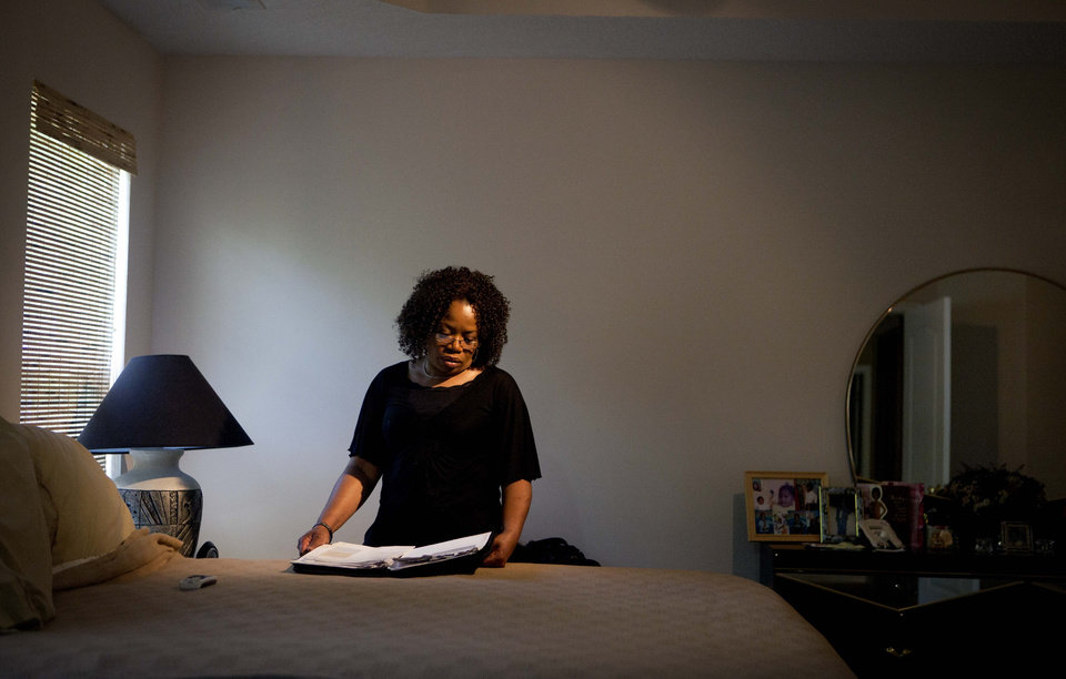 Photo -   Patricia Jackson sifts through bank documents in the bedroom of her home Saturday, June 16, 2012, in Marietta, Ga. On a suburban cul-de-sac northwest of Atlanta, the Jacksons are struggling to keep a house worth $100,000 less than they owe. Their voices and those of many others tell the story of a country that, for all the economic turmoil of the past few years, continues to believe things will get better. But until it does, families are trying to hang on to what they've got left. The Great Recession claimed nearly 40 percent of Americans' wealth, the Federal Reserve reported last week. The new figures, showing Americans' net worth has plunged back to what it was in 1992, left economists shuddering. (AP Photo/David Goldman)