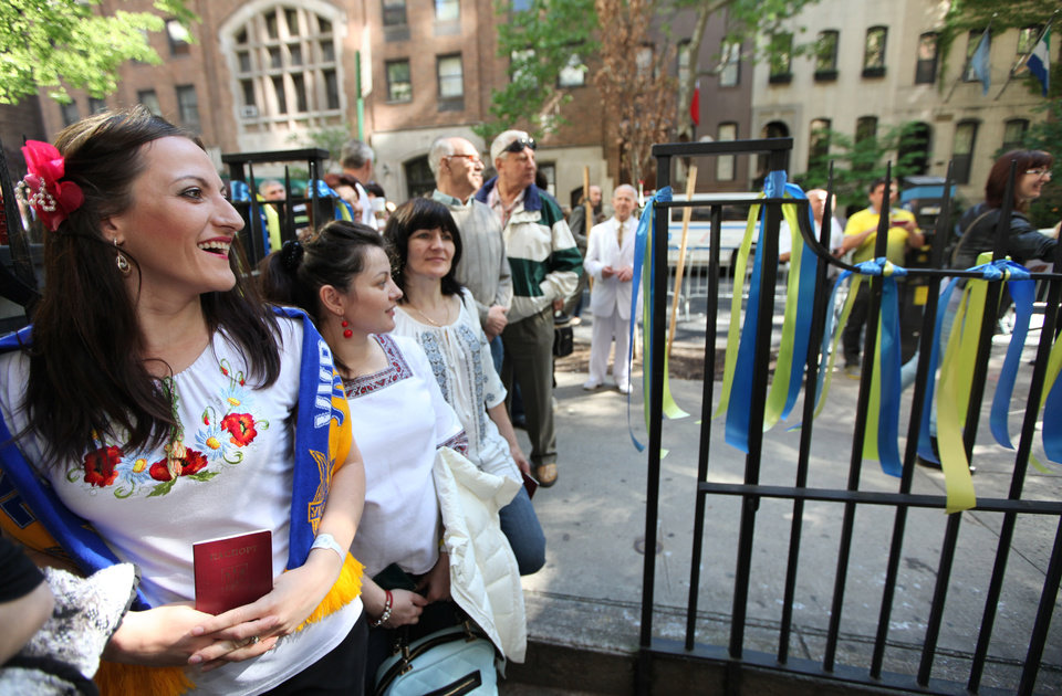 Photo - Oksana Golab, her sister Olesya Semenyak and mother, Halyna Smenyak, all of Clifton, N.J., watch people  pose for pictures outside the Ukrainian Consulate in New York Sunday Mary 25, 2014.  (AP Photo/The Record of Bergen County, Kevin R. Wexler) ONLINE OUT; MAGS OUT; TV OUT; INTERNET OUT;  NO ARCHIVING; MANDATORY CREDIT Ukrainians from the tri-state area and beyond went to the Ukrainian Consulate in New York City on Sunday to vote for their country's new president.  Twenty-one voters left on a bus from St. Nicholas Ukrainian Catholic Church in Passaic.  Ukraine has had an interim president since their revolution this winter.  Sunday May 25, 2014. STAFF PHOTO BY; KEVIN R. WEXLER   (AP Photo/Northjersey.com)