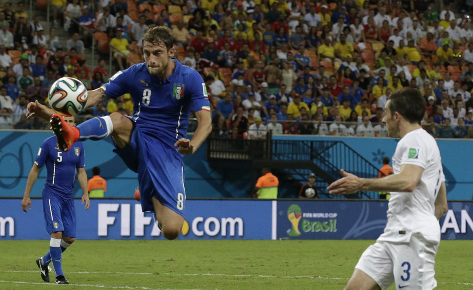 Photo - Italy's Claudio Marchisio, left, controls the ball in front of England's Leighton Baines, right, during the group D World Cup soccer match between England and Italy at the Arena da Amazonia in Manaus, Brazil, Saturday, June 14, 2014. (AP Photo/Matt Dunham)