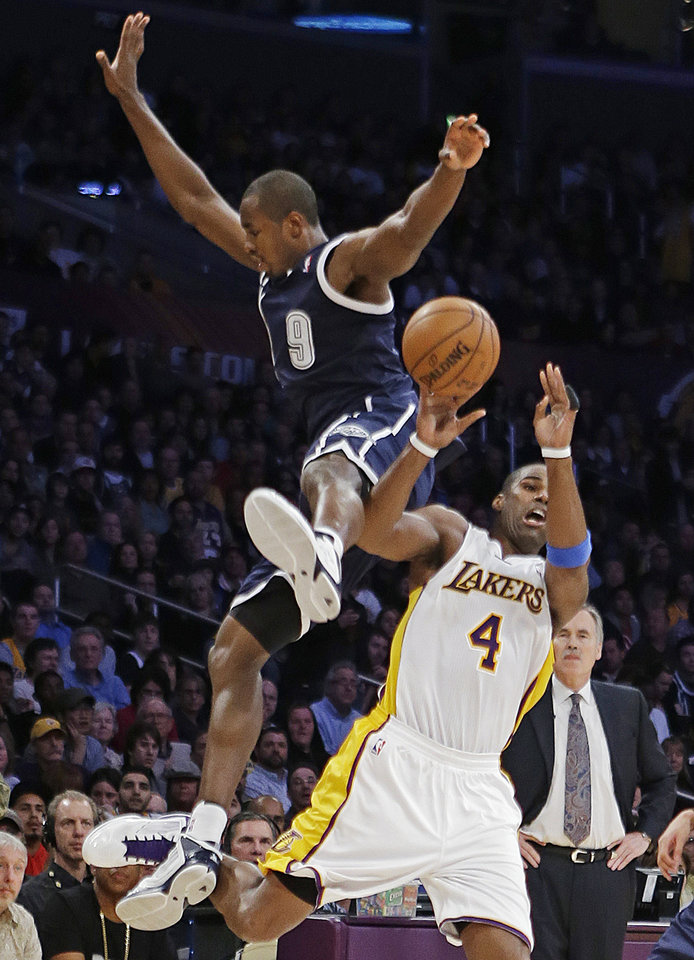 Photo - Oklahoma City Thunder forward Serge Ibaka (0), of the Republic of Congo, and Los Angeles Lakers forward Antawn Jamison (4) collide while going for possession of the ball in the first half of an NBA basketball game in Los Angeles, Sunday, Jan. 27, 2013. (AP Photo/Reed Saxon)