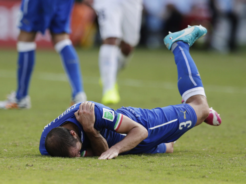 Photo - Italy's Giorgio Chiellini holds his shoulder after Uruguay's Luis Suarez ran into it with his teeth during the group D World Cup soccer match between Italy and Uruguay at the Arena das Dunas in Natal, Brazil, Tuesday, June 24, 2014. (AP Photo/Petr David Josek)