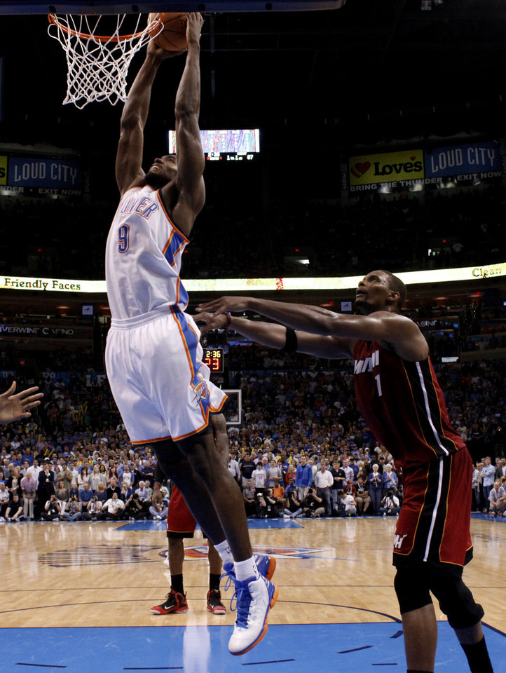 Photo - Oklahoma City's Serge Ibaka (9) dunks in front of Miami Heat's Chris Bosh (1) during the NBA basketball game between the Miami Heat and the Oklahoma City Thunder at Chesapeake Energy Arena in Oklahoma City, Sunday, March 25, 2012. Photo by Sarah Phipps The Oklahoman