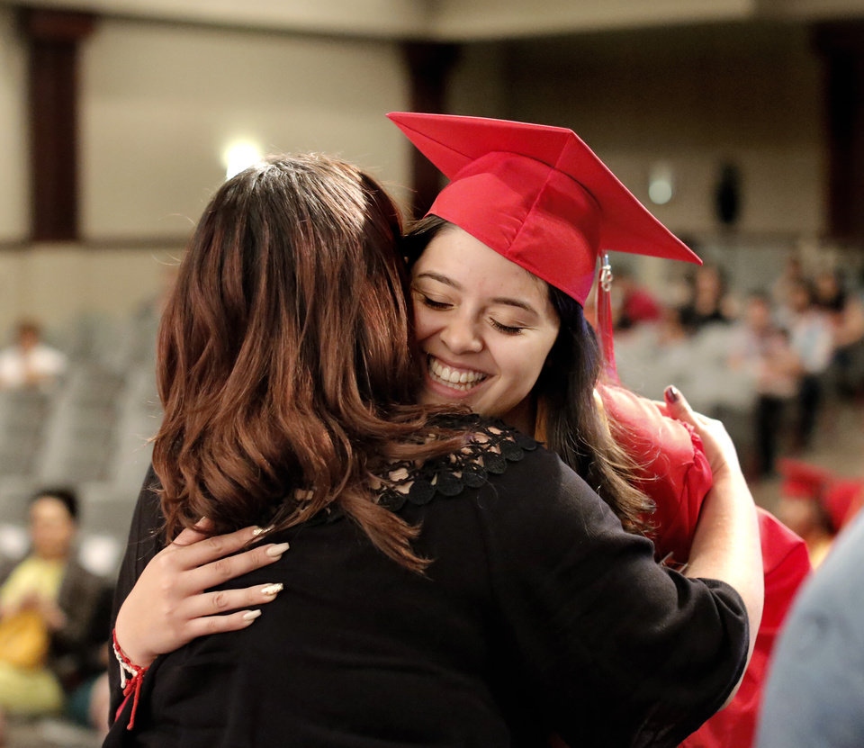 Photo - Michelle Guereca pauses to hug a faculty member  as she walks across the stage during a special graduation ceremony to recognize 30 (ELL) English Language Learners at U.S. Grant High School. The ceremony was Monday afternoon,  May 21, 2018.  Photo by Jim Beckel, The Oklahoman