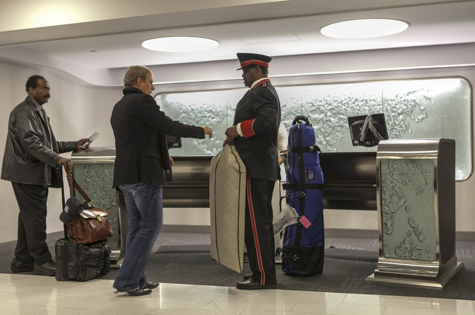 In this Thursday, March 14, 2013 photo,Singer and songwriter Michael Bolton, middle, is assisted by skycap Frederick Pearson, right, as he arrives at American Airlines Flagship Check-in terminal at Los Angeles International Airport, LAX. American\'s Flagship Check-in service, a VIP discreet and expedited check-in process offers personal access to agents for assistance with check-in and bag check, and a separate security line when flying through LAX and now Miami International Airport. (AP Photo/Damian Dovarganes)
