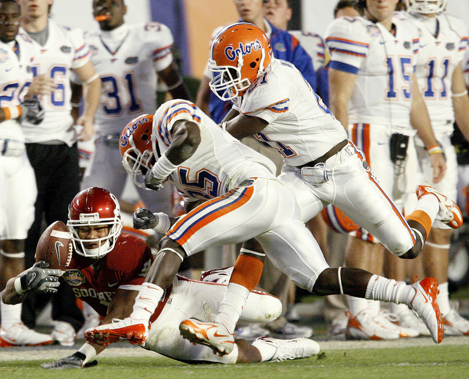 Photo - OU's Juaquin Iglesias drops a pass in front of Florida's Ahmad Black, center, and Major Wright during the second half of the BCS National Championship college football game between the University of Oklahoma Sooners (OU) and the University of Florida Gators (UF) on Thursday, Jan. 8, 2009, at Dolphin Stadium in Miami Gardens, Fla. 