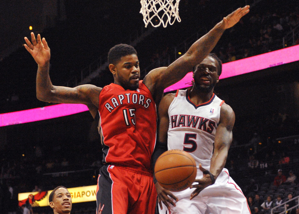 Photo - Atlanta Hawks forward DeMarre Carroll (5) passes around Toronto Raptors' Amir Johnson (15) in the first half of their NBA basketball game Tuesday, March 18, 2014, in Atlanta. (AP Photo/David Tulis)