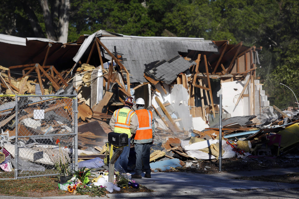 Photo - Demolition experts watch as the home of Jeff Bush is destroyed Monday, March 4, 2013,  in Seffner, Fla.  A sinkhole opened up underneath the house late Thursday, Feb. 28, 2013,  evening swallowing Bush, 37.  The 20-foot-wide opening of the sinkhole was almost covered by the house, and rescuers said there were no signs of life since the hole opened Thursday night.  (AP Photo/Scott Iskowitz)