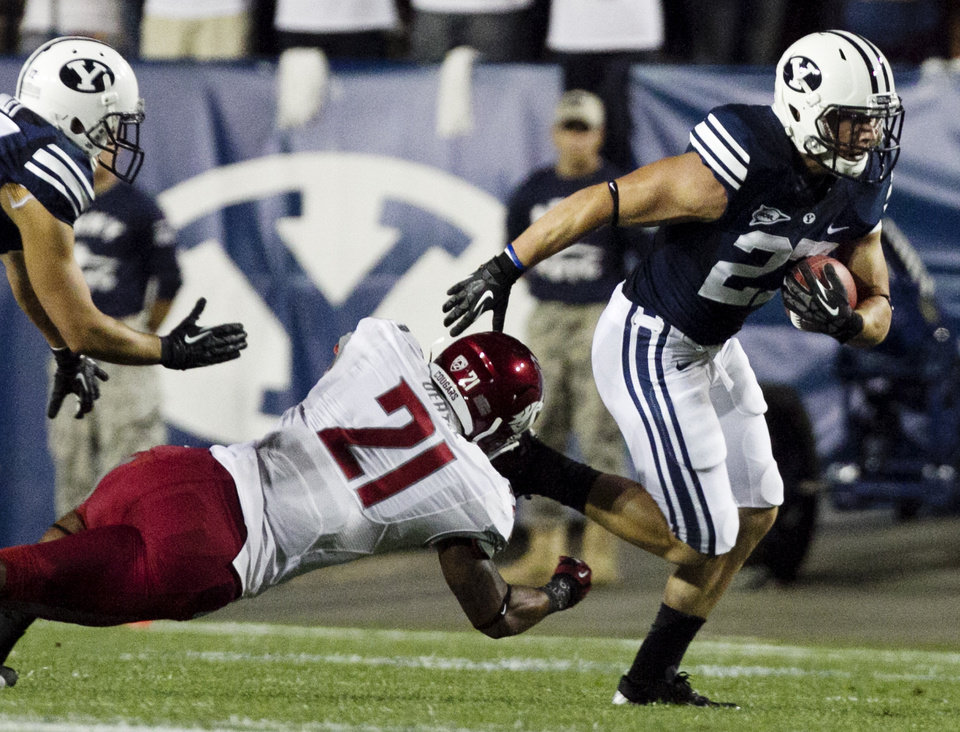 Photo -   BYU's David Foote evades a tackle by Washington State's Eric Oertel during the first half of the NCAA college football game between the BYU Cougars and the Washington State Cougars at LaVell Edwards Stadium in Provo, Utah on Thursday, Aug. 30, 2012. (AP Photo/Spenser Heaps, Daily Herald)
