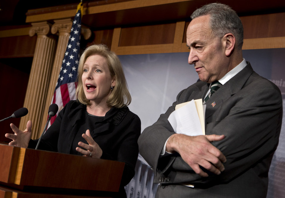 Photo - Sen. Kirsten Gillibrand, D-N.Y., left, and Sen. Charles Schumer, D-N.Y., right, react after the Senate passed a $50.5 billion emergency relief measure for Superstorm Sandy victims at the Capitol in Washington, Monday, Jan. 28, 2013. Three months after Superstorm Sandy devastated coastal areas in much of the Northeast, the Senate is finaly sending a $50.5 billion emergency package of relief and recovery aid to President Obama for his signature. (AP Photo/J. Scott Applewhite)