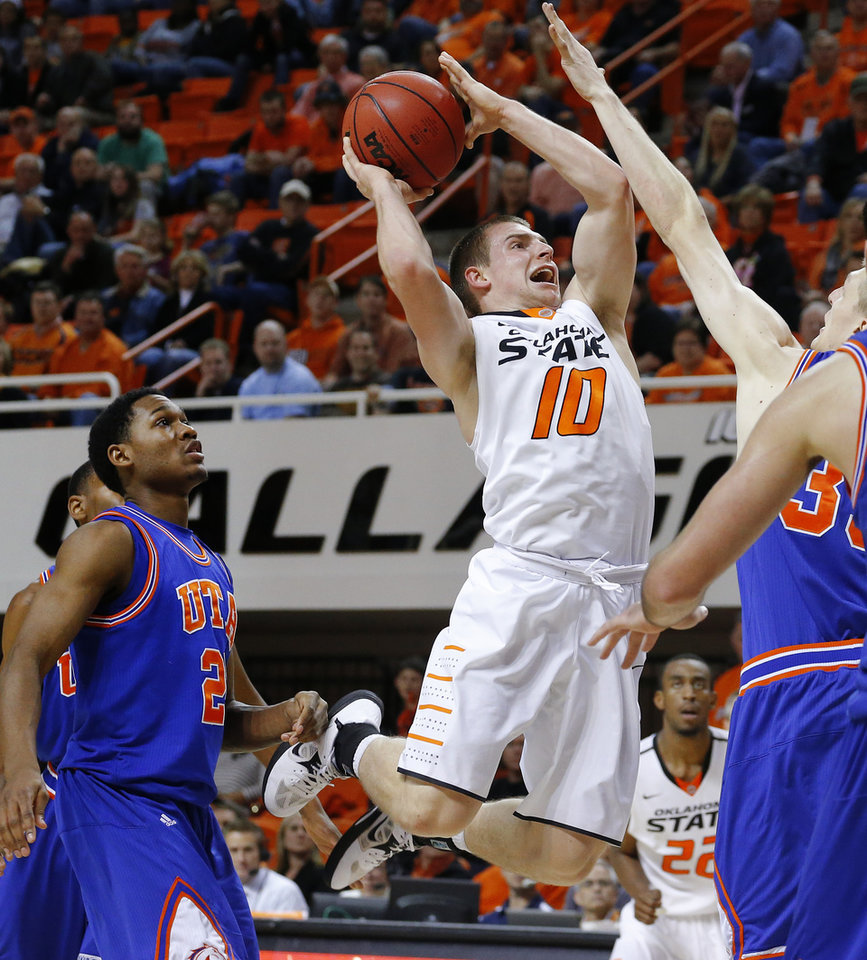 Photo - Oklahoma State's Phil Forte (10) goes past Texas-Arlington's Kevin Butler (24) during a college basketball game between Oklahoma State University and UT Arlington at Gallagher-Iba Arena in Stillwater, Okla., Wednesday, Dec. 19, 2012. Photo by Bryan Terry, The Oklahoman