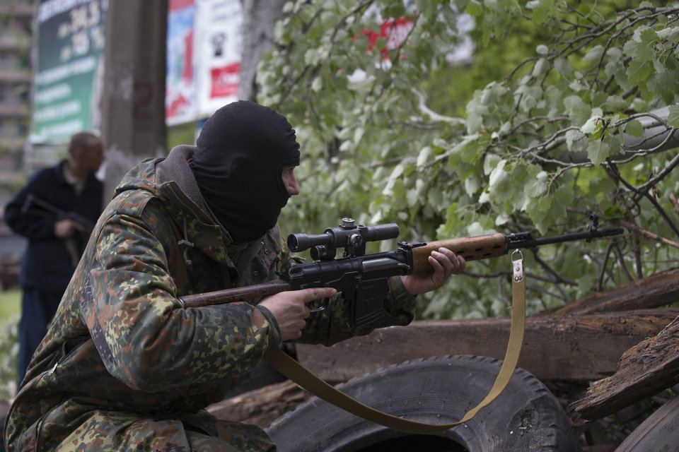Photo - A Pro-Russian gunman aims his weapon behind barricades in Slovyansk, eastern Ukraine, Friday, May 2, 2014. Ukraine launched what appeared to be its first major assault against pro-Russian forces who have seized government buildings in the country's east, with fighting breaking out Friday in a city that has become the focus of the insurgency. (AP Photo/Alexander Zemlianichenko)