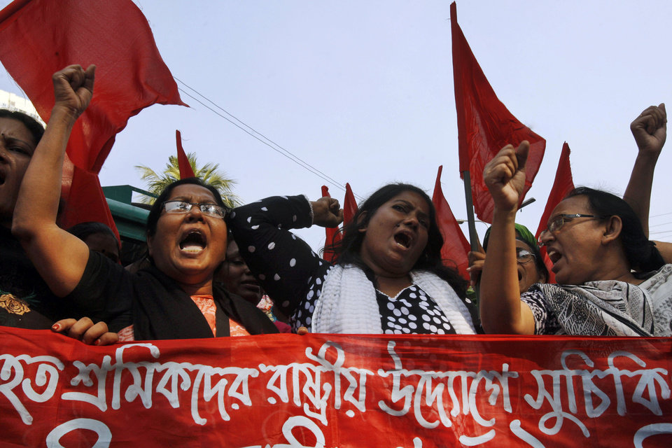 "Bangladeshi garment workers shout slogans as they participate in a protest to mourn the death of the victims of a fire in a garment factory in Dhaka, Bangladesh, Friday, Nov. 30, 2012. Hundreds of garment workers protested Friday outside the Bangladeshi factory where 112 people were killed by the fire, demanding compensation for their lost salaries. The banner reads: ""We demand financial help for the workers."" (AP Photo/Pavel Rahman)"