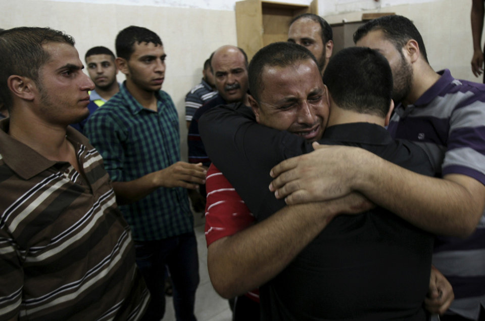 Photo - Palestinian relatives comfort each other after they saw the body of Ahmad Jarboua, 25, who was killed in an Israeli strike with other two people, at Najar hospital in Rafah refugee camp, in the southern Gaza Strip, Tuesday, Aug. 26, 2014. Three men were killed and five were wounded in a strike on a group of men east of Rafah near the waste water treatment plant, according to Gaza health official Ashraf al-Kidra. (AP Photo/Eyad Baba)